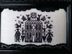 Man and woman standing beside house black and white cross stitch