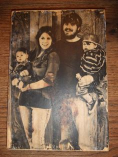 Print your picture out on plain paper, Take piece of wood and coat with mod podge, turn picture upside down on wood press and let dry overnight. next day using water and your hands rub paper off of wood (your picture will be on the wood) now cover with more mod podge... Modge Podge FTW!