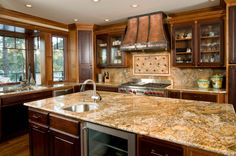 Beautiful wood kitchen with a hint of rustic design.  Interesting how the backsplash matches the countertop.