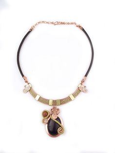 """Wire Wrapped Necklace """"Shira."""" Mixed metal copper and bronze hammered twice-wrapped black Goldstone pendant with a leather band."""