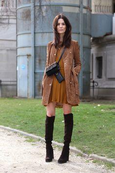 Hedvig Opshaug posa para foto de street style usando vestido plissado camelo, trench coat de suede marrom e botas de camurça over the knee pretas