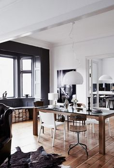 Home Design The Dining Space Finished In Black And White With Large Glass Top Dining Table With White Chair And Wooden Chair Alongside Animal Fur Rug And Stack Of Books On The Floor Stylish Home In Contrasting Colors And With A Personality