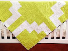 """this beautiful, modern quilt has an aztec inspired pattern on the front using a mix of a vibrant limeaid and bright white fabrics. cotton batting is sandwiched between high quality fabrics. the finished quilt measures 39""""x48.5"""" and is hand bound for a perfectly clean edge. the size is great for snuggling your babe and is big enough to grow with your toddler.BACKING: fading arrow print in plum. BINDING: black and white. hand bound. this quilt is ready to shi..."""