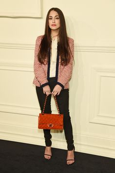 Audrey Gelman in a tweed jacket, black pants, and black ankle strap heels at Chanel's Paris-Salzburg show in NYC