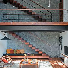 Dois lances de escada interligam a garagem, na parte alta do terreno, à sala. Mãos-francesas metálicas fixam cada um dos degraus de ipê na parede. Sobre o piso de tijolos, tapete da By Kamy.