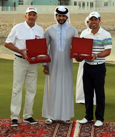 His Highness Shaikh Nasser Bin Hamad al Khalifa (He is the eldest son of the King of Bahrain Hamad bin Isa Al Khalifa) presents the prize to the team winners Paul Casey of England (R) and Joe Montana of the USA (L) during the second day of the Bahrain Invitational at the Royal Golf Club on14  Apr 2012 in Riffa.