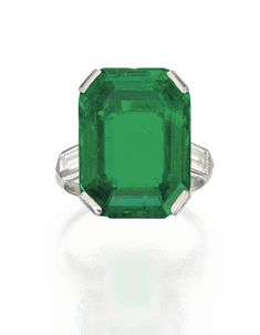 Platinum, Emerald and Diamond Ring Centered by an emerald-cut emerald weighing approximately 15.23 carats, flanked by two baguette diamonds weighing approximately .80 carat, size 6¾; circa 1930.