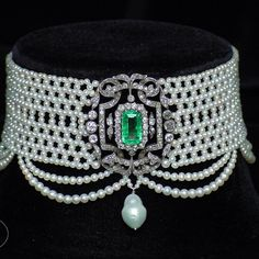 Woven seed pearl choker with graduated pearl drapes and antique white gold, diamond and emerald and pearl drop brooch.