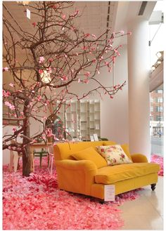 Blossom tree VM so I get that it's a window display. But I'm also convinced that a tree so lovely indoors is a fab idea!  Love the carpet of petals and THAT yellow velvet mustard lounging sofa!!!
