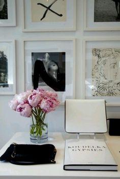 desk. flowers and frames.