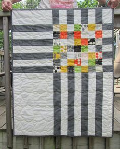 Trendy little crib quilt for a mod baby OR a perfect wall hanging for the modern home. This gem features fabrics from Comma designed by Zen Chic for Moda fabrics. Small squares in the middle lead out to a mottled grey and off white stripes on the outer edges. Quilt measures 30 x 38. The back of the quilt is yellow with grey comma shapes. Binding is mottled grey, stitched down by machine using a decorative stitch for durability. Quilted by machine in large waves. Machine washable in cold…