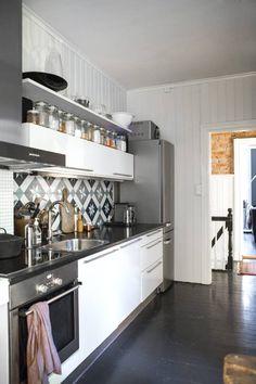 MAROKKANSK INNSLAG: Innredningen er fra HTH, ogflisene over kjøkkenbenken er fraFar-fars fliser. Bak skimtes den råmursteinsveggen i gangen.styling: Silje Aune Eriksen