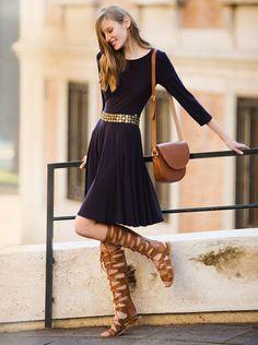 Vestido con vuelo en azul marino con sandalias de caña alta romanas, cinturón oro y bandolera en color tierra. Un sofisticado y cómodo look para el verano.