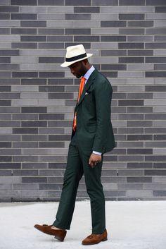 Dark green suit, orange tie, brown loafers, hat