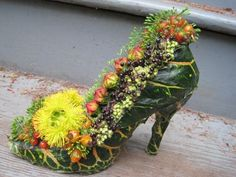 A flower arrangement in a shoe! Floral Designer Francoise Weeks uses a woodland look for her arrangements. Awesome!