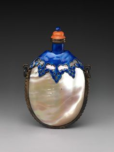 """19th century Chinese snuff bottle.  Mother-of-pearl with brass fittings and blue enamel, red glass stopper. 3""""high."""