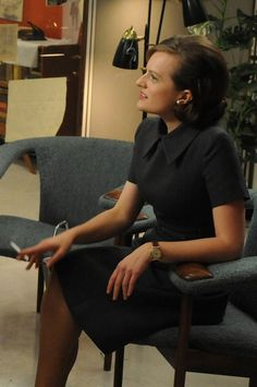In one of her final dresses of season four, Peggy wears a smart navy shift dress with sharp collar to gossip about Don's engagement—to Megan, his secretary—with Joan.