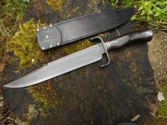 a little bowie knife commision i have just finished . the blade is 12.25 inch long 40mm wide give or take and 6mm thick at the spine bearing steel . etched finish with polished edge and clip  the guard , fittings and pomel cap are wrought iron with brass spacers and pins  the handle is african blackwood , sheath is vegtan leather