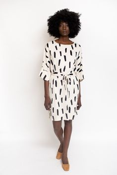 Just Female Agnete Dress is an effortless dress featuring 3/4 wide sleeves, attached belt, boat neck in an ivory and black brush stroke print. Model is 5'9