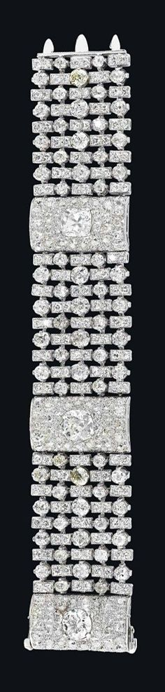 AN ART DECO DIAMOND BRACELET, BY BULGARI Designed as a wide mesh band of alternated circular-cut diamonds and rectangular-shaped diamond-set links, enhanced by three pavé-set diamond bombé spacers, centering upon two cushion-shaped and one circular-cut diamonds, mounted in platinum, late 1930s, 19.4 cm Signed Bulgar