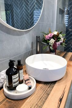 Contemporary bathroom with navy subway herringbone feature wall and grey tiles, custom timber vanity and sleek tapware