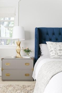 Stunning master bedroom with tufted navy blue velvet wingback headboard and bed frame, paired with patterned gray and white bedding, a gray campaign-style nightstand with gold corners and brass hardware, and an architectural geometric base gold lamp with white linen shade.