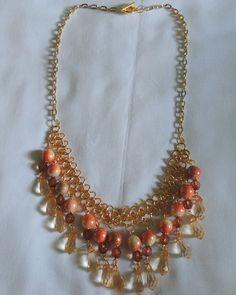 Colar de correntes dupla dourada com pérolas laranja, pedras transparentes marrom e pingente transparente marrom claro. R$ 42,00