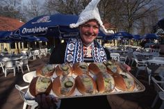 Herring Vendor in Traditional Dutch Clothing -A waitress in costume holds up a tray of herring and bread. Keukenhof, the Netherlands. 1997
