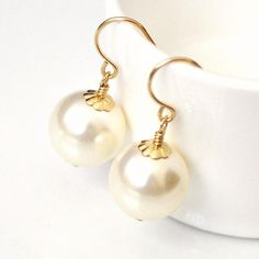 Large Pearl Drop Earrings!This design has been made with CRYSTALLIZED� - Swarovski Elements.All components 14kt gold fill.Available in WHITE or IVORY - please state preference in checkout.Stunning Swarovski pearls (12mm) capped with gold flower-design caps.View all bridal jewelry here: http://www.etsy.com/shop/somethingjeweled--------------------------QUANTITY DISCOUNTSBuy 4-5 items from this shop and receive 10% offBuy 6  items from this shop and receive 15% offPlease...