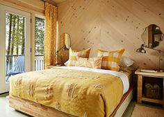 """Sarah says: """"This new bedroom was created from what used to be a storage area. I installed a wall to convert it to two-thirds sleeping quarters (complete with a sink) and one-third closet. Installing wide pine boards in a chevron style creates interest on the wall — and eliminates the need for a headboard.""""   - CountryLiving.com"""