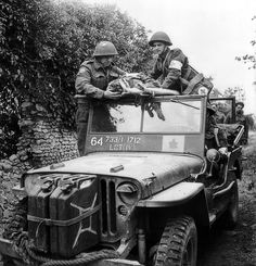 Canadian soldiers assist a wounded soldier in a modified Jeep Willys MB used as an ambulance.