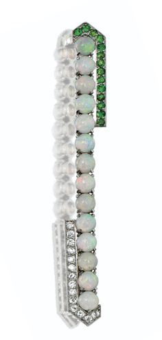 AN ART DECO OPAL, DEMANTOID GARNET & DIAMOND BAR BROOCH, CARTIER, CA 1925.  Set with a row of 14 round cabochon opals partly bordered on one side by 14 round demantoid garnets & on the opposite side by 14 old European-cut diamonds, mounted in platinum, signed Cartier, numbered 3016610.