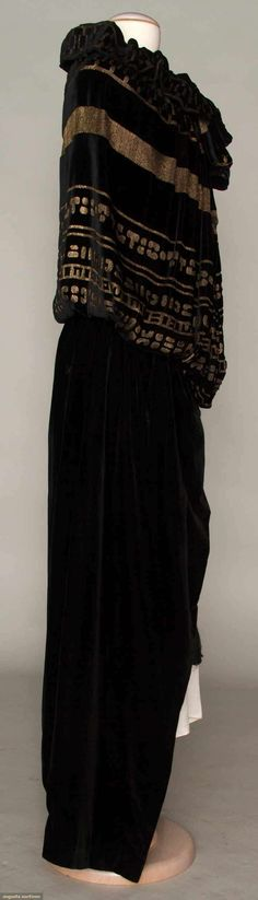 VELVET & LAME EVENING CAPE, c. 1915 Black silk velvet long cape, blouson top w/ rows of gold lame hieroglyphics, at back sides 2 black silk tasseled cords to either tie in front or hang down back, black silk charmeuse lining. Sideway