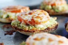 Tomato and cheese on avocado and tuna on an English muffin