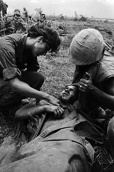 Freelance woman war correspondent Jurate Kazickas, from New Rochelle, N.Y., comforts a wounded U.S. Marine after he was hit near the South Vietnamese village of Con Thien, July 4, 1967. The Marines were moving into an area near the demilitarized zone to recover Marine bodies when they were hard hit by North Vietnamese in the Vietnam War. (AP Photo/Henri Huet)