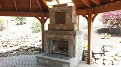 Covered outdoor fireplace with a koi pond and landscaping