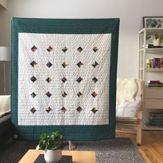 Modern%20handmade%20oversized%20throw%20quilt%20in%20cream%20and%20rich%20teal,%20with%20accents%20of%20blue,%20burgandy,%20marigold%20and%20orange.%20Machine%20pieced%20and%20quilted%20with%20hand-stitched%20navy-blue%20binding.%20Backing%20fabric%20is%20the%20same%20rich%20teal%20colour.%20Made%20from%20100%%20reclaimed%20cotton%20fabrics%20and%20all-natural%20cotton%20batting.%20Original%20patternApprox%20size%20:%2055%22%20x%2064%22