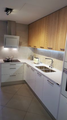 Roma handle by Viefe in a kitchen which combines white and wood.