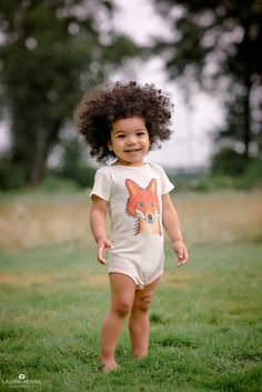 Smiling boy in a grassy field wearing a fox onesie.