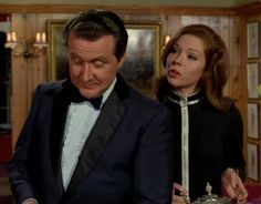 Series 5 - John Steed wears a midnight blue tuxedo with black satin notch collar piping on the trouser legs. The jacket is fastened with a single cloth covered button, and the skirt has two long vents. It's worn with a ruffled pale blue dress shirt, deep midnight blue velvet bow tie and black dress shoes. This tux was worn in 5 episodes.  Emma is sporting one of her catsuits with silver trim.