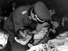 Tweede Wereldoorlog, bezetting : In opdracht van rijkscommissaris dr.  Seyss-Inquart verzorgt de Duitse ordepolitie warm eten voor 2.000 tot  3.000 arme Amsterdamse kinderen in het Koloniaal Instituut (Tropen  Instituut, Tropenmuseum) te Amsterdam. De kleinsten worden zelfs  gevoerd. Nederland datum onbekend [waarschijnlijk 13 januari 1941].