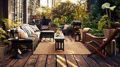Hemtrevlig lounge uteplats med KUNGSHOLMEN loungekombination i svart och tät växtlighet