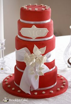 Red Monogram Cake by Brooklyn Cake. This cake features a tall design, with satin ribbon, a monogram plate, gumpaste flowers with edible pearls.