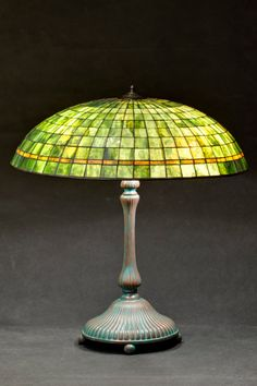 Tiffany stained glass green parasol lamp. Green and amber lamp shade. American glass lamps. Lotus lamp base. Classic green lamp.