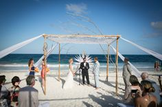 Ryan's and Jesse's beach ceremony with a creative wedding tent made of driftwood and a fishing net. Photo: Michael Segal Photography