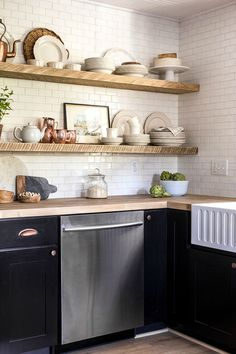 Nice kitchen design idea. Wood open shelves, white tile, black cabinets with brass handles