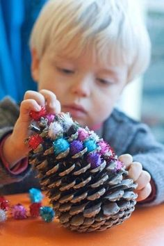 Kid's holiday DIY: clue pom poms into a pinecone to make a colorful, mini christmas tree.: