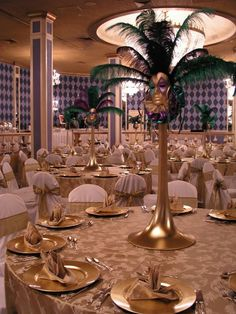 Gold table cloth and gold and white plates with tall vase mask center piece Masquerade Party Centerpieces, Masquerade Ball Decorations, Masquerade Ball Party, Mardi Gras Centerpieces, Masquerade Theme, Masquerade Wedding, Mardi Gras Decorations, Graduation Centerpiece, Feather Centerpieces