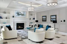 White marble surrounds this enclosed fireplace, topped by a classic white wood mantle. Bright blue accents add visual interest to the white leather chairs and sofa.