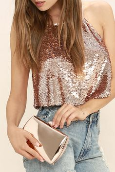 "If there's one accessory you can see yourself wearing over and over, it's the Reflected Image Rose Gold Mirrored Clutch! Reflective, rose gold vegan leather covers this structured clutch with matching metal trim. Top clasp opens to interior accordion sides. Carry as a clutch or attach the 50"" rose gold chain strap."